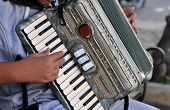 pic of accordion  - Young adult playing old accordion in the streets of Iraklion Crete - JPG