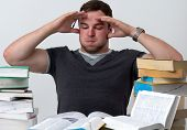 stock photo of overwhelming  - Young Student overwhelmed with studying with piles of books in front of him - JPG