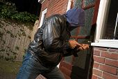 stock photo of bandit  - A burglar trying to get into a house by the backdoor - JPG