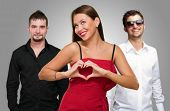 pic of threesome  - Woman Standing In Front Of Men Making A Heart Shape Sign On Gray Background - JPG