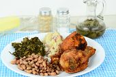 image of southern  - Black eyed peas and turnip greens with deep fried chicken legs and potatoes with a jar of spicy vinegar sauce on blue gingham place mat - JPG