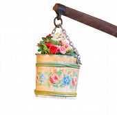 stock photo of shadoof  - Pail with mixed flowers hanging from a sweep over white background - JPG