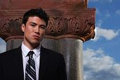 stock photo of lobbyist  - Young biracial businessman standing before a column - JPG