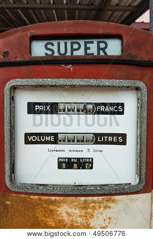 A Vintage Antique Gasoline Fuel Pump On Red
