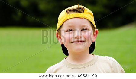Happy child wearing yellow ball cap in outdoor portrait