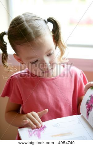 Little Toddler Girl Writing At School Desk