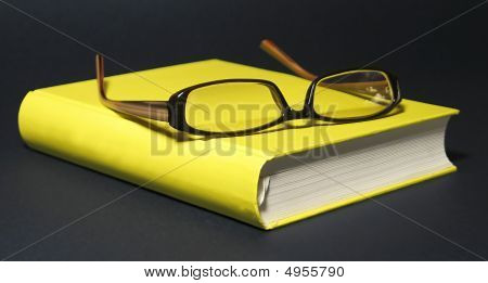 Eyeglasses On The Yellow Book