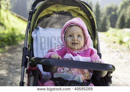 Smiling Pretty Little Child Girl In Buggy On Nature
