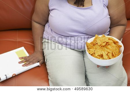 Woman sitting on couch with magazine and crisps mid section
