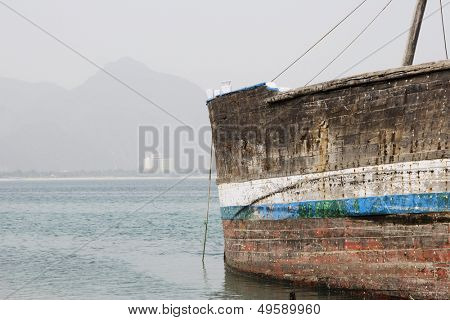 Khor Fakkan UAE old wooden dhow washed up on shore in front of Khor Fakkport