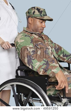 Sad US Marine Corps soldier wearing camouflage uniform in wheelchair assisted by female nurse