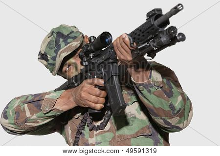 US Marine Corps soldier aiming assault rifle against gray background