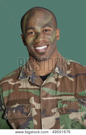 Portrait of an African American male US Marine Corps soldier with camouflaged face over green background