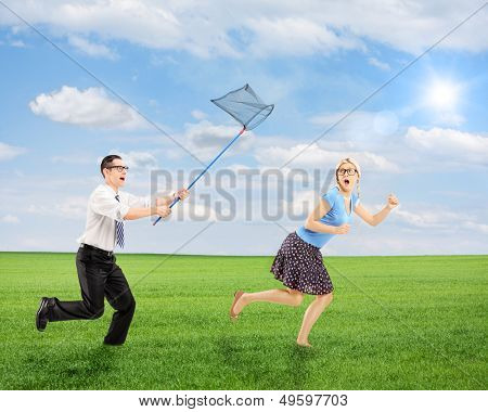 Scared young female trying to runaway from man running with butterfly net outdoor