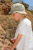 stock photo of paleontologist  - Boy geologist tap a rock formation with a hammer - JPG