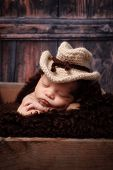 foto of baby cowboy  - 9 day old newborn baby boy wearing a crocheted cowbow hat and sleeping in a wooden crate - JPG
