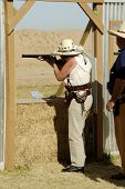 image of wild west  - woman competitor shooting a lever action rifle in a cowboy shoot competition - JPG