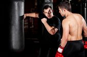 stock photo of punch  - Latin Boxer and his coach practicing some moves on a punching bag at a gym - JPG