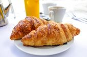 stock photo of croissant  - Breakfast with coffee and croissants in a basket on table - JPG