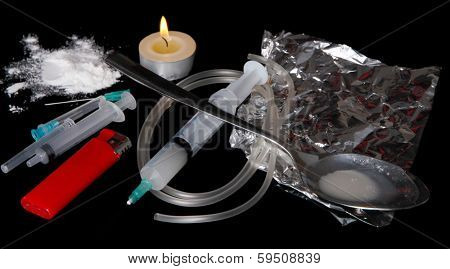 Heroin in spoon and syringes on black background