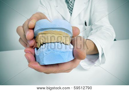 a dentist sitting in a desk showing a dental mould