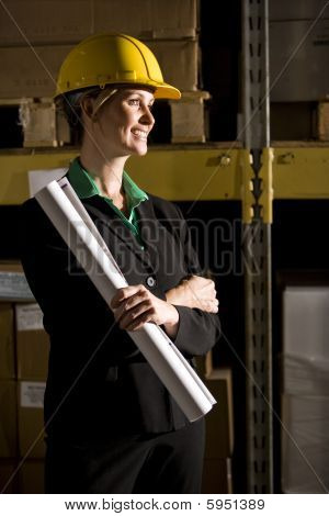 Businesswoman in storage warehouse holding plans