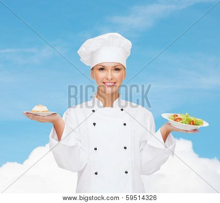 cooking and food concept - smiling female chef, cook or baker with salad and cake on plates