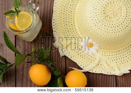 Fresh Squeezed Lemonade on a rustic wooden table with lemons and a yellow sun hat. Horizontal format with an oldtime feel, shot from a high angle.