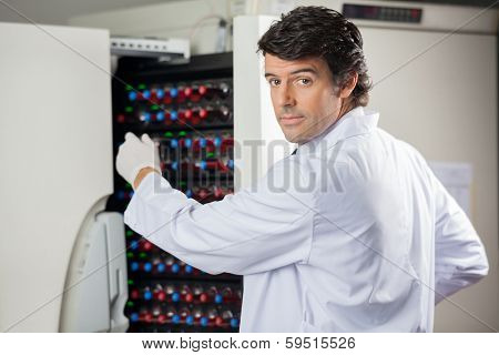 Portrait of male researcher placing bottles into blood culture instrument