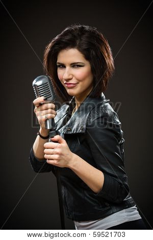 Half-length portrait of female rock singer wearing black jacket and handing microphone on grey background. Concept of music and rave
