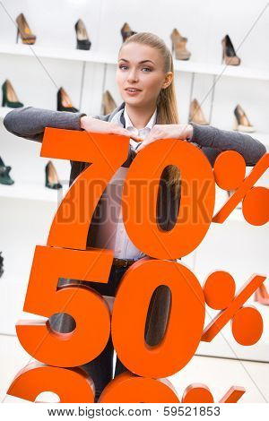 Woman showing the percentage of sales on high heeled shoes in the shopping center against the window case with shoes