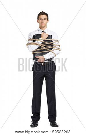 Full-length portrait of businessman handing briefcase who tied with the line, isolated on white. Concept of slavery and violence