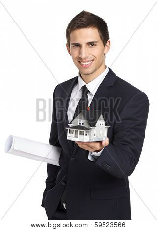 Half-length portrait of businessman who hands model house and layout, isolated on white. Concept of real estate and business
