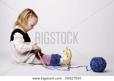 little girl knitting scarf