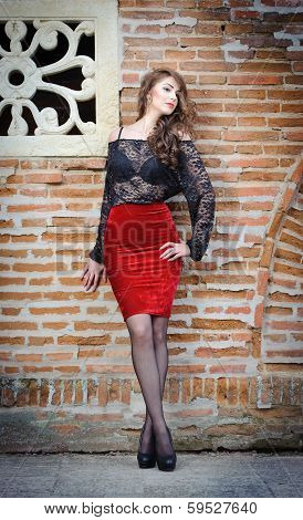 Charming young brunette woman in black lace blouse, red skirt and high heels near the brick wall