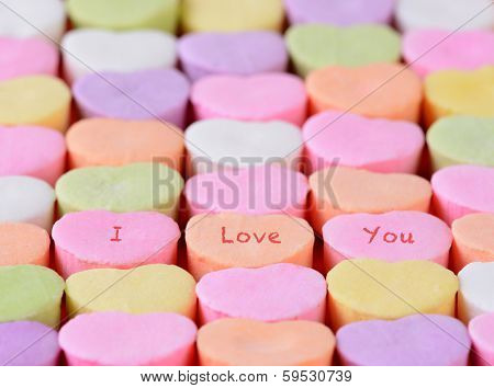 Closeup of the words I Love You spelled out on candy hearts.  The hearts are arranged in straight rows only candies have words. Shallow depth of field. Great for Valentine's Day projects.