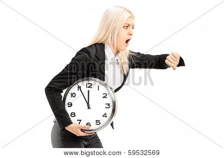Young businesswoman running late with a wall clock in her hand isolated on white background
