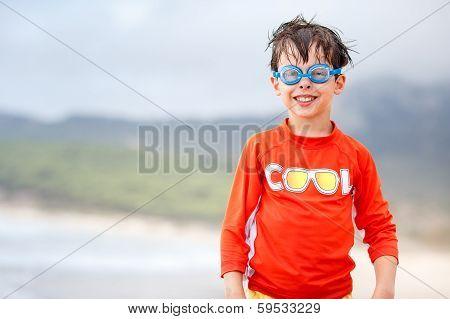 Cute little boy in blue swim goggles on beach