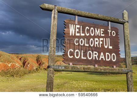 welcome to colorful Colorado roadside wooden sign with red sandstone cliff in background