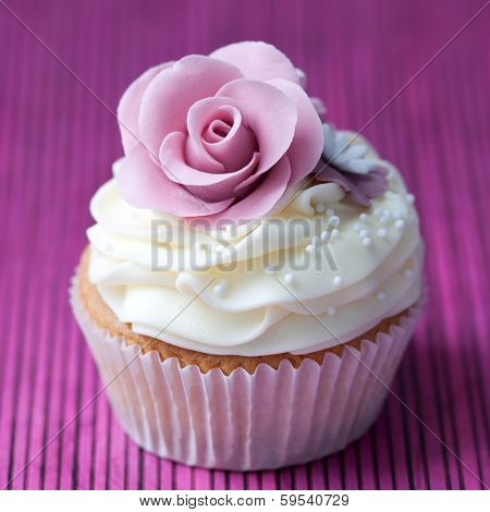 Cupcake decorated with a purple sugar rose