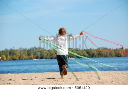 Child Running And Playing With Ribbons