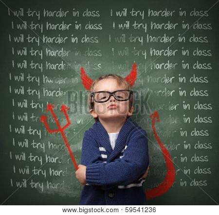 Naughty devil schoolboy with lines written on a blackboard reading I will try harder in class and devils horns, tail and pitchfork. Detention and school discipline / punishment concept