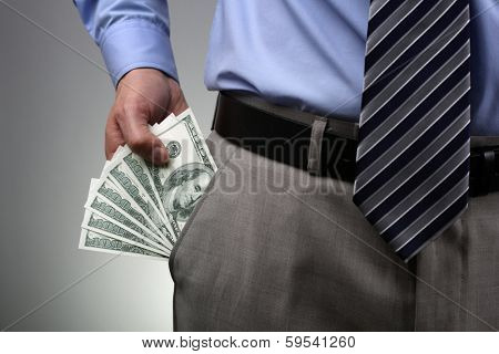 Businessman with money in suit trouser pocket concept for business wealth, paying, corruption or bribing