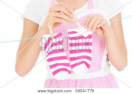 A midsection of a woman hanging up socks over white background