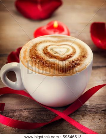 Valentine's Day Coffee with heart on foam. Heart drawing on cappuccino or latte art coffee. Love. Valentine art design. Coffee cup on a wooden table, heart shaped candle, rose petals and satin ribbon