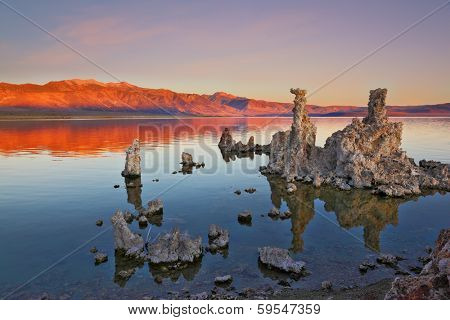The magic of Mono Lake. Outliers -calcareous tufa formation on the smooth water of the lake. Orange sunset