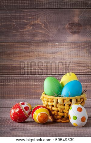 easter color eggs in basket on wooden background