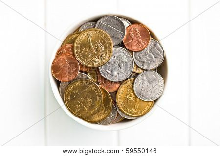 U.S. coins in ceramic bowl on wooden table