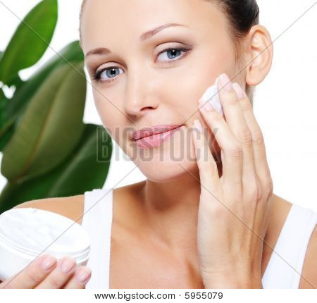 Woman Holding Moisturizer Cream And Applying It On Her Face