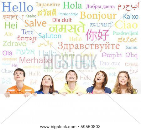 Group of teenagers over the background with the many words from the different languages (language school concept)
